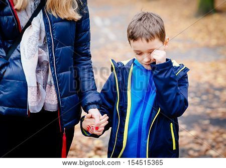 Boy Crying And Holding His Mother Hand During The Walk