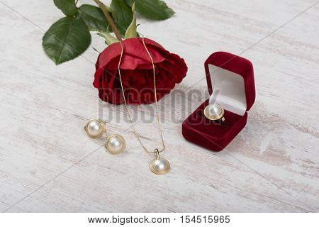 Jewelry set of golden ring in a gift box, earrings, necklace with pearls and red rose on white wooden background
