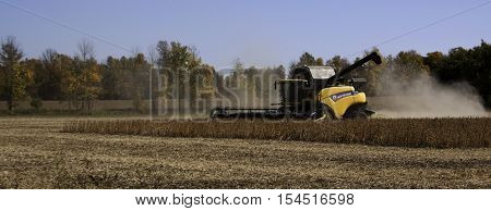 Brockville, ON, October 7, 2016 -- Close up side view of large yellow combine harvester clearing and seeding a grain field near Brockville, Ontario on a bright sunny cloudless day in October