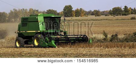 Brockville, ON, October 7, 2016 -- Close up of large green combine harvester clearing and seeding a grain field near Brockville, Ontario on a bright sunny cloudless day in October