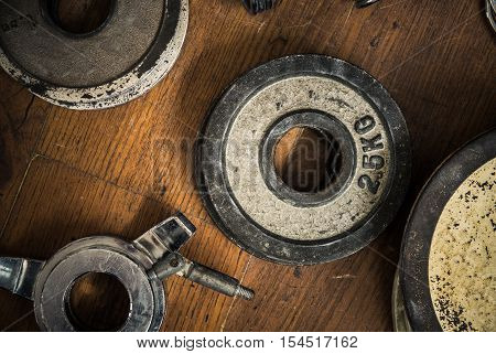 Detail Of Some Vintage Gym Dumbbell Weights Against A Rustic Wooden Floor