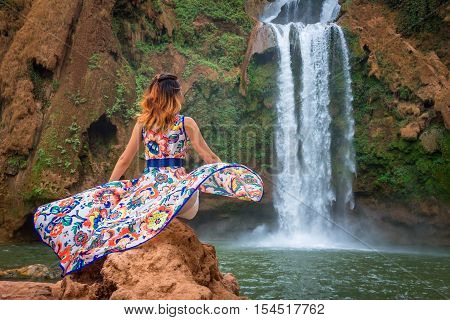Beautiful waterfall in Morocco. Back woman beautiful dress looking fall Ouzoud Grand Atlas. Exotic nature North Africa poster