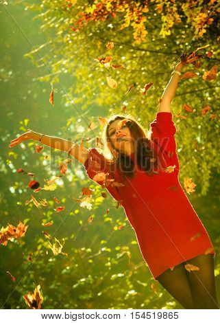 Woman playing with autumnal leaves. Young girl in park tossing foliage. Nature outdoor relax scenery concept.