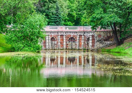 Rastrelli grotto in Lefortovo Park in Moscow. The XVIII century building of brick with white stone columns with carved decorations on the shore of the pond. Summer landscape