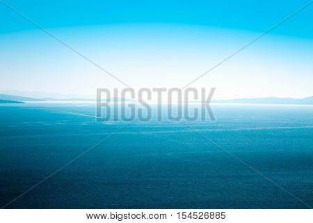 Beautiful Blue Sea and Sky. Islands in Haze on the Horizon. Aerial View. Summer Seascape with Clear Water. Serene Ocean and Tranquility Concept. Copy Space Background. Toned Photo.