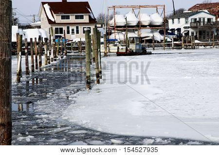 An ice breaking boat breaks up the ice at the Babylon Village Docks during a cold winter