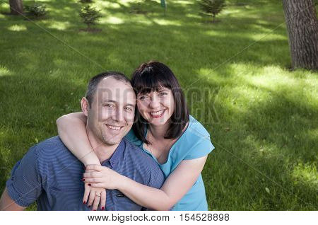Happy couple man and woman relaxing in the summer park