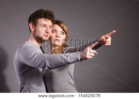 Fear and scare. Two young terrified scared people. Stressed woman and man showing to copy space. Couple afraid of bad things war.