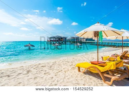 Sunbed and umbrella at Maldives island with white sandy beach and sea