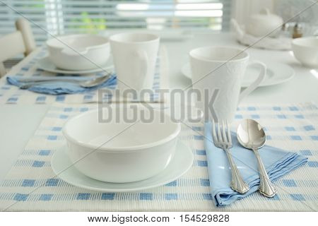 Blue and white create a simple elegant table setting. Extremely shallow depth of field. Shot in natural light.