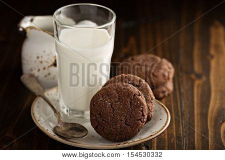Chocolate cookies with a glass of milk in dark rustic setting