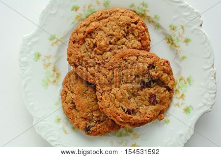Fresh baked oatmeal raisin walnut cookies on pretty vintage plate from overhead in horizontal format