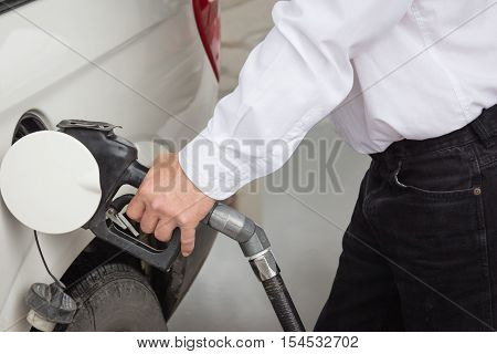 close up horizontal image of a male hand filling his gas tank on the car.