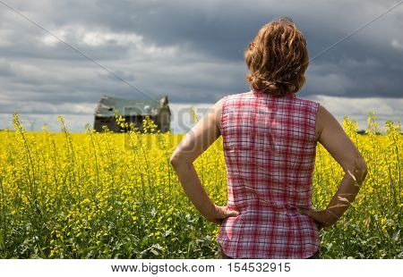 horizontal image of a farmers wife standing at the edge of a yellow canola field wearing a red checkered shirt  looking over the field at  dark stormy rain clouds forming in the sky in the summer time