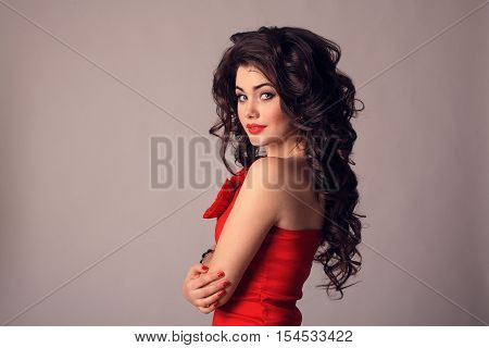 The girl with brunette hair on a gray background. The concept of beauty and fashion.