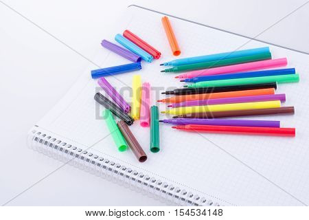 Colorful felt-tip pens on a notebook on a white background