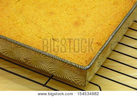 Fresh baked golden cornbread baked in vintage tin on black cooling rack in horizontal format. Shallow depth of field. Selective focus on the cornbread.