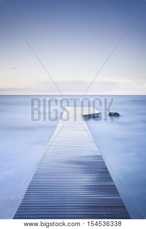 Wooden pier or jetty rocks and calm sea. Long Exposure