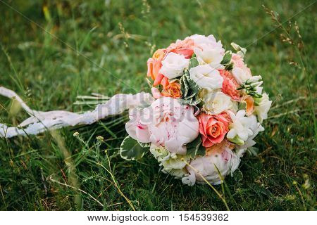 Wedding bouquet . The bride's bouquet. Bouquet of red and pink flowers black berries and greenery with a ribbon of color Marsala lies on a log by the lake
