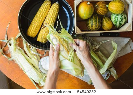 woman prepares corn for cooking in a bowl top view from self