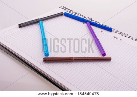 Color felt-tip pens form a house shape on white background