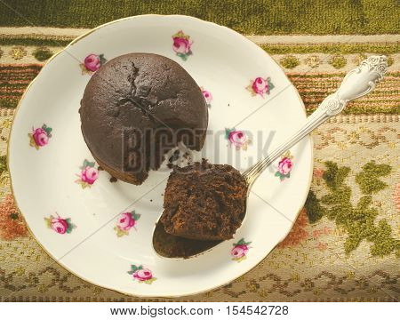 Chocolate fondant, souffle cake with whipped cream on decorative plate, top view, toned
