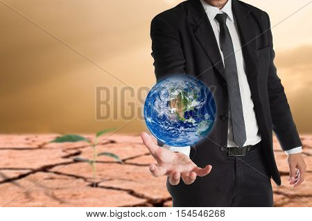 Businessman holds Earth in a hand global warming concept. Elements of this image are furnished by NASA