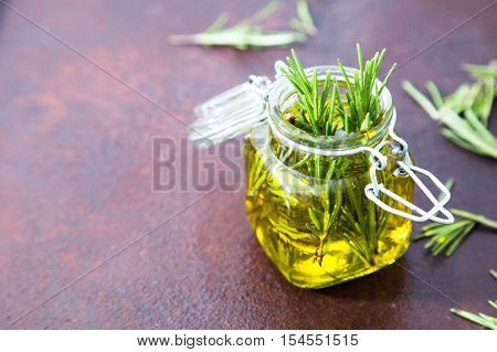 Rosemary Oil. Rosemary Essential Oil Jar Glass Bottle And Branches Of Plant Rosemary With Flowers On
