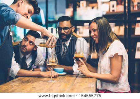 Customers looking at barista pouring fresh coffee from shaker in wine glass