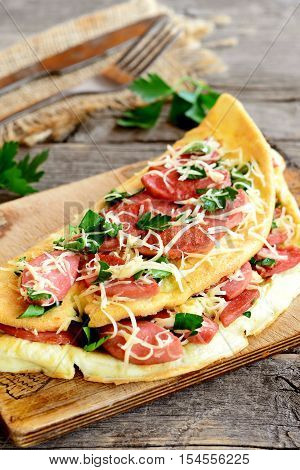 Egg omelette with grated cheese and fried sausages on a board, fork, knife, burlap, fresh parsley leaves on old wooden table. Delicious omelette recipe. Closeup