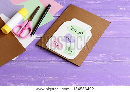 Paper greeting card with jar, colored hearts and wishes. Scissors, colored paper sheets, white cardboard, glue stick, black marker on wooden background. Fun kids art concept