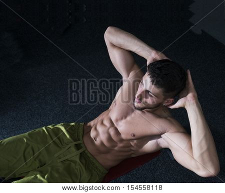Fit athlete man doing one hand push up at gym