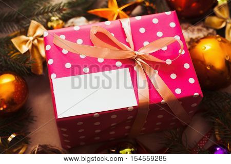 Pink gift box with blank card under Christmas tree. Free space on paper sheet on package, golden decorating balls and xmas tree branches frame.