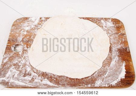 Rolled dough on wooden cutting board, free space. Close-up on raw pastry on kitchen table, void. Bakery, homemade cuisine, confectionery concept