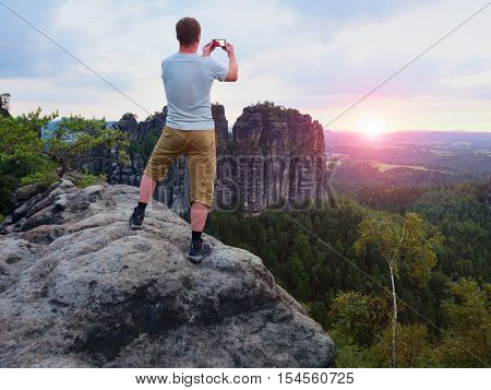 Short Hair Man On Cliff Of Rock Takes Photo. Sunny Evening In Rocky Mountains.