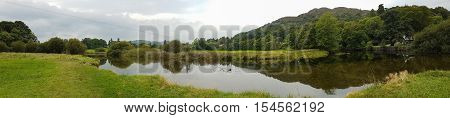 Wide Panoramic view of pond and beautiful reflections in Ambleside countryside Cumbria UK