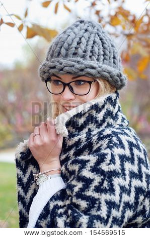 Student girl in autumn park wearing glasses warm cardigan and thick knitted hat. Fall street style city look.