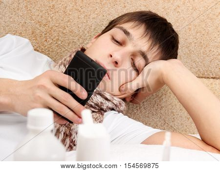 Teenager with Cellphone on the Sofa at the Home