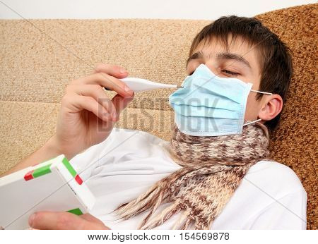 Sick Teenager in Flu Mask with pack of pills on the Sofa at the Home