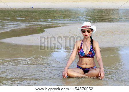 Women body beautyful bikini hat and sunglasses on Thung Wua Lan Beach at Chumphon Provice Thailand.
