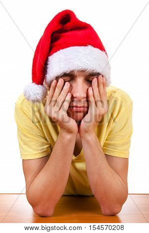 Sad Young Man in Santa's Hat at the Table Isolated On The White Background