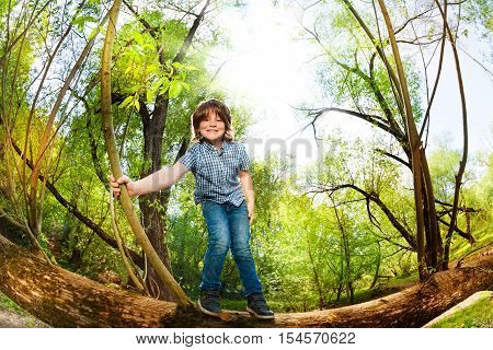 Portrait of happy ten years old boy having fun standing on the trunk of fallen tree in the forest