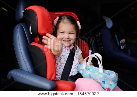 baby girl sitting in a red children's car seats and smiling