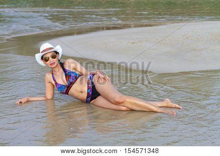 Women beautyful bikini hat and sunglasses on Thung Wua Lan Beach at Chumphon Provice Thailand.