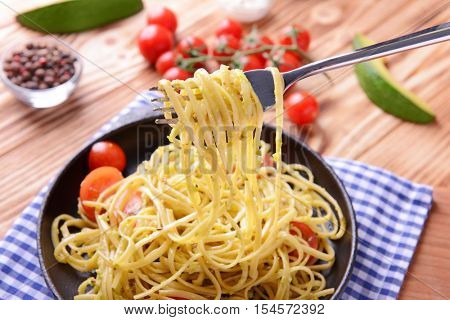 Pasta with avocado sauce impaled on fork, closeup