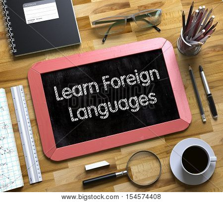 Learn Foreign Languages on Small Chalkboard. Learn Foreign Languages - Red Small Chalkboard with Hand Drawn Text and Stationery on Office Desk. Top View. 3d Rendering.