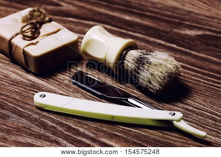 Men's cosmetics shaving brush and razor on a wooden background