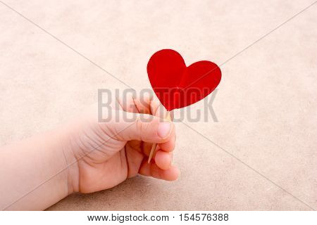 Little red color heart shape at the top of a stick in hand