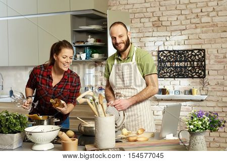 Happy couple cooking together at home, in kitchen.