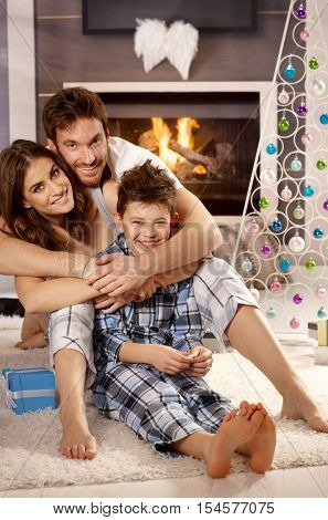 Happy little family hugging on floor at christmas morning, looking at camera.